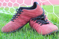Röda skor på grönt gräs med målfotboll Royaltyfri Bild