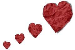 Röda skrynkliga pappers- hjärtor formar att sväva på, isolerat på vit bakgrund royaltyfri bild