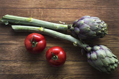Röda smakliga söta italienska tomater och kronärtskockor på trälodisarna royaltyfria bilder