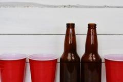 Röda solo plast-koppar och två ölflaskor Arkivbilder