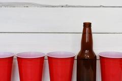 Röda solo plast-koppar och två ölflaskor Royaltyfri Bild