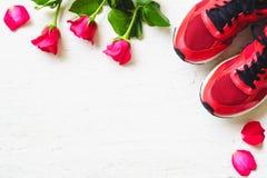 Röda sportskor och röda rosor på vit träbakgrund, Valen Royaltyfri Foto