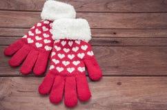 Röda stack vinterhandskar på träyttersida Arkivfoton