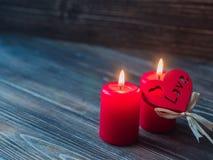 Röda stearinljus för valentin, förälskelsehjärta över mörk träbakgrund, utrymme för text Arkivbild