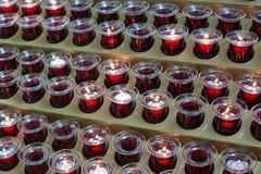 Röda stearinljus i en katolsk kyrka Fotografering för Bildbyråer