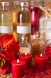 Röda stearinljus och oljor Arkivfoto