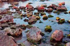 Röda stenar i vattnet arkivbild