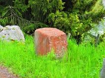 Röda stenblock bland det grönt och grått royaltyfria foton
