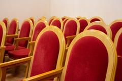 Röda stolar i en tom konserthall arkivfoton