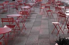 Röda stolar på och utomhus- trottoar i en storstad sent på natten Arkivbild