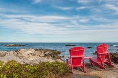 Röda stolar som vänder mot den Keji sjösidastranden & x28; Södra kust, Nova Scotia, royaltyfri fotografi