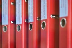 Röda stora mappmappar med inskrifter för att lagra kontorsdokument står vertikalt på en hylla arkivfoto