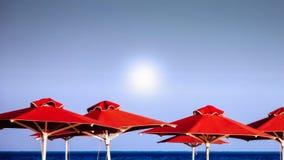 Röda strandparaplyer Royaltyfri Foto