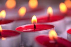Röda tända Tealights med den guld- flamman Royaltyfri Fotografi