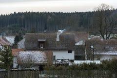 Röda tak av byhus med snörest och lampglas Arkivfoto