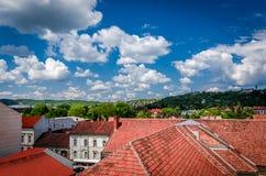 Röda tak vs molnig himmel Arkivfoton