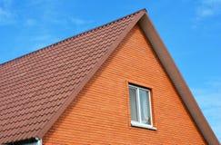 Röda tegelplattor för tak för hus för metallark Metalltaksinglar - taklägga konstruktion, loftyttersida som taklägger reparation Royaltyfria Bilder