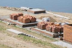 Röda tegelstenar som staplas i högar på konstruktionsplatsen Royaltyfria Foton