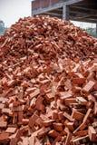 Röda tegelstenar som staplas på konstruktionsplatser Arkivbild