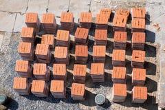 Röda tegelstenar som utanför läggas i paletter Arkivbild