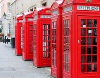 5 röda telefonaskar i London Arkivfoton