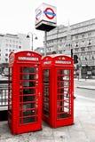 Röda telefonaskar och underjordisk logo, London, Royaltyfria Foton