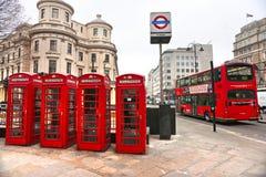 Röda telefonaskar och underjordisk logo, London, Arkivfoto