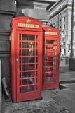 Röda telefonbås för Londoner i en gata Royaltyfri Fotografi