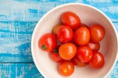 Röda tomater i en bunke på en blå träbakgrund Royaltyfri Bild