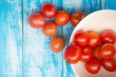 Röda tomater i en bunke på en blå träbakgrund Arkivfoton