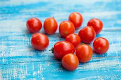 Röda tomater i en bunke på en blå träbakgrund Royaltyfria Foton
