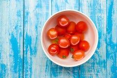 Röda tomater i en bunke på en blå träbakgrund Fotografering för Bildbyråer