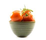 Röda tomater i en grön kopp på en vit bakgrund Arkivfoto