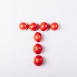 Röda tomater i formen av bokstaven T Royaltyfri Fotografi