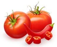 Röda tomater med gröna sidor och chilipeppar med stycken Royaltyfri Bild