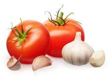 Röda tomater med gröna sidor och vitlök med kryddnejlikor Arkivfoton