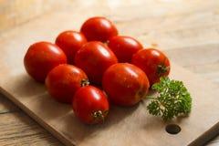 Röda tomater och en kvist av persilja på en träskärbräda Arkivfoton
