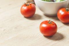 Röda tomater och en vit bunke Royaltyfri Bild