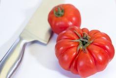 Röda tomater och kniv Fotografering för Bildbyråer
