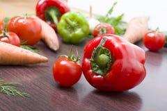 Röda tomater och paprikor på en tabell på bakgrunden av grönsaker Nya tomater och peppar på en träbrun tabell Royaltyfria Foton