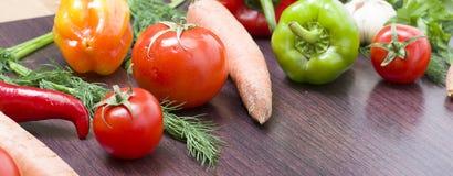 Röda tomater och paprikor på en tabell på bakgrunden av grönsaker Nya tomater och peppar på en träbrun tabell Arkivfoton
