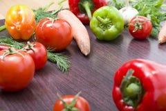 Röda tomater och paprikor på en tabell på bakgrunden av grönsaker Nya tomater och peppar på en träbrun tabell Arkivbilder