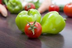Röda tomater och paprikor på en tabell på bakgrunden av grönsaker Nya tomater och peppar på en träbrun tabell Royaltyfri Foto