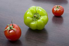Röda tomater och paprikor på en tabell på bakgrunden av grönsaker Nya tomater och peppar på en träbrun tabell Royaltyfri Bild