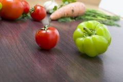 Röda tomater och paprikor på en tabell på bakgrunden av grönsaker Nya tomater och peppar på en träbrun tabell Fotografering för Bildbyråer