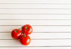 Röda tomater på den vita tabellen Arkivbild
