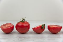 Röda tomater på den vita wood tabellen Arkivbilder