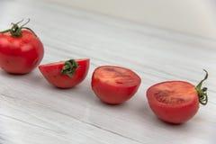Röda tomater på den vita wood tabellen Arkivfoto