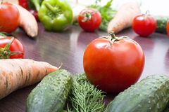 Röda tomater på en tabell på en bakgrund av grönsaker Nya tomater på en träbrun tabell Royaltyfri Fotografi