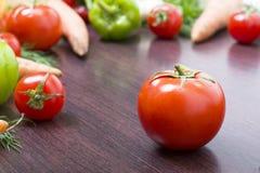 Röda tomater på en tabell på en bakgrund av grönsaker Nya tomater på en träbrun tabell Fotografering för Bildbyråer